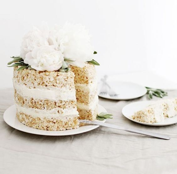 a krispie rice wedding cake with white cream and fresh white peonies and greenery on top looks very elegant