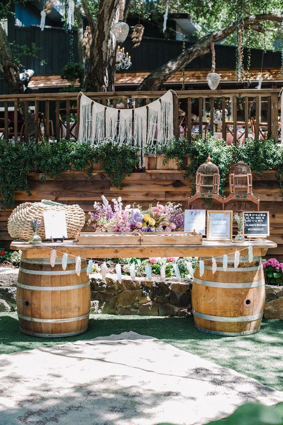 a lovely boho wedding gift table with barrels and a desktop, a basket, pastel blooms, cages, a feather bunting and a macrame hanging