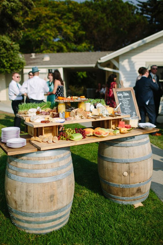 a lovely wedding fruit bar with barrels and a tiered countertop with grass, fruits and berries plus a chalkboard sign