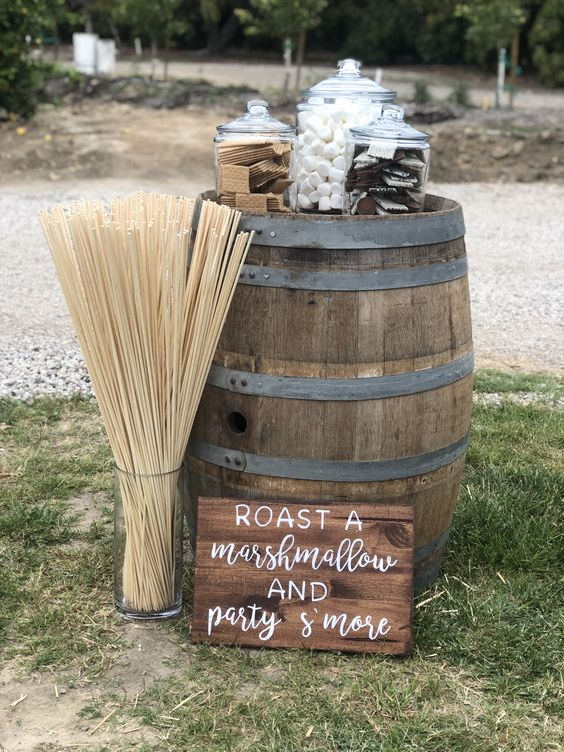 a mini barrel s'mores bar with a sign, some sticks, cookies, marshmallows and chocolate in jars for an outdoor wedding space