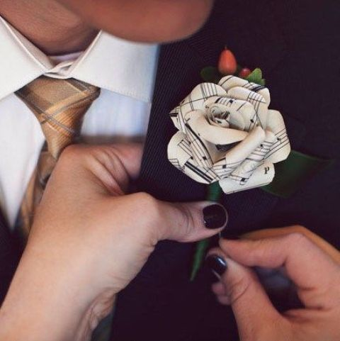 a music note wedding boutonniere with berries and a green ribbon for a music-loving wedding