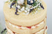 a naked wedding cake with strawberries and wild blooms plus cork cake toppers in bright colors
