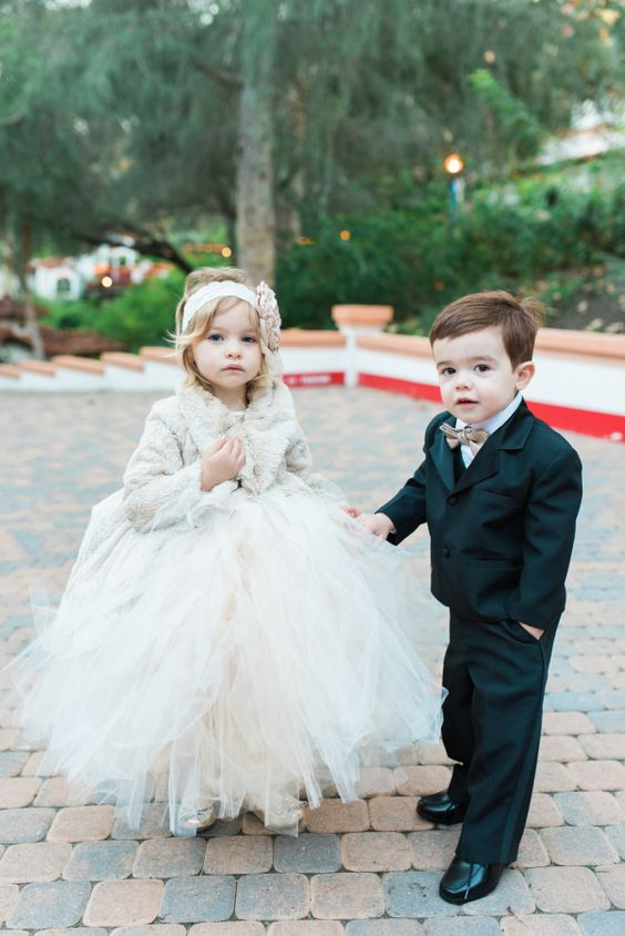 a neutral faux fur coat, a white tulle skirt, glitter shoes and a fabric headband for a winter flower girl look