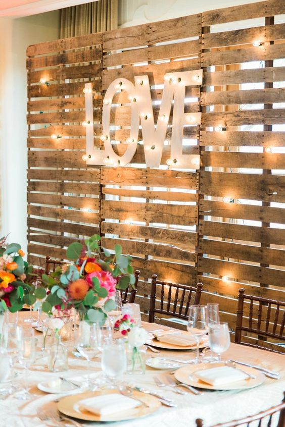 a pallet backdrop with lights and large marquee letters is a nice idea for the wedding venue backdrop
