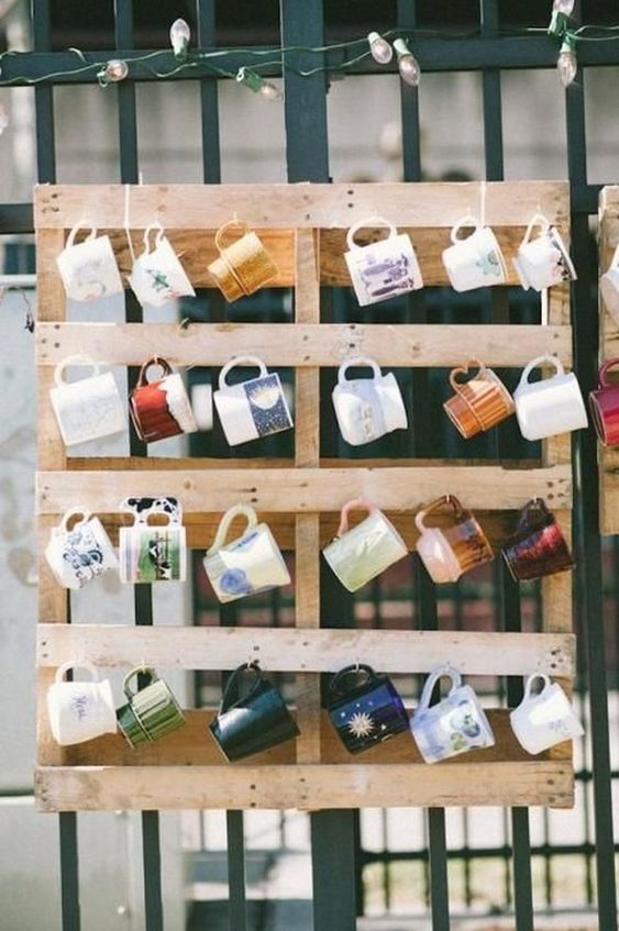 a pallet with mugs hanging is a cool idea to offer your wedding gifts