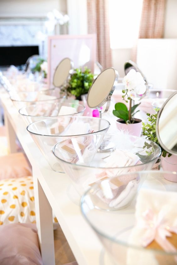 a pastel spa bridal shower setting with beautiful potted blooms and greenery, mirrors and glass bowls, treatments and pillows