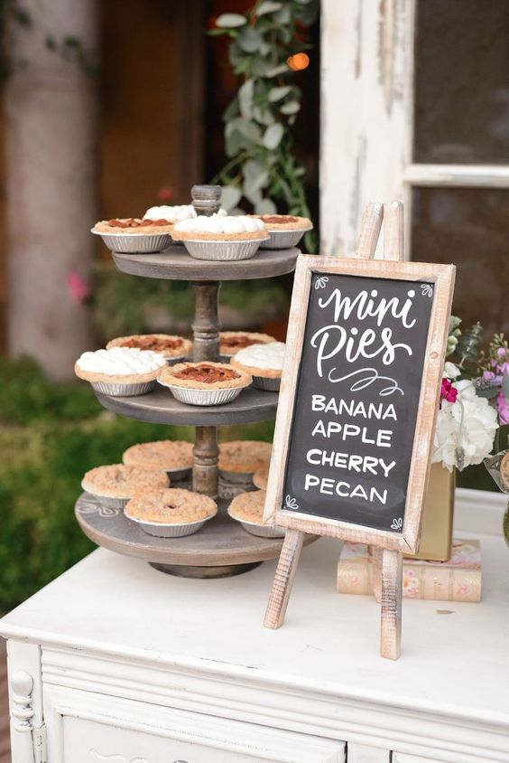 a pie bar with a wooden stand with mini pies, a chalkboard sign and some bold blooms on a vintage book is very cute