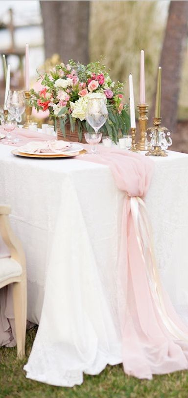 a pink tulle table runner adds tenderness to the table and matches the wedding centerpiece with pink blooms