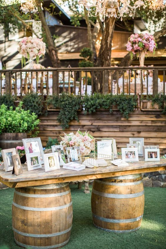 a pretty wedding decoration   barrels with a tabletop, family pics in frames, neutral and pastel blooms