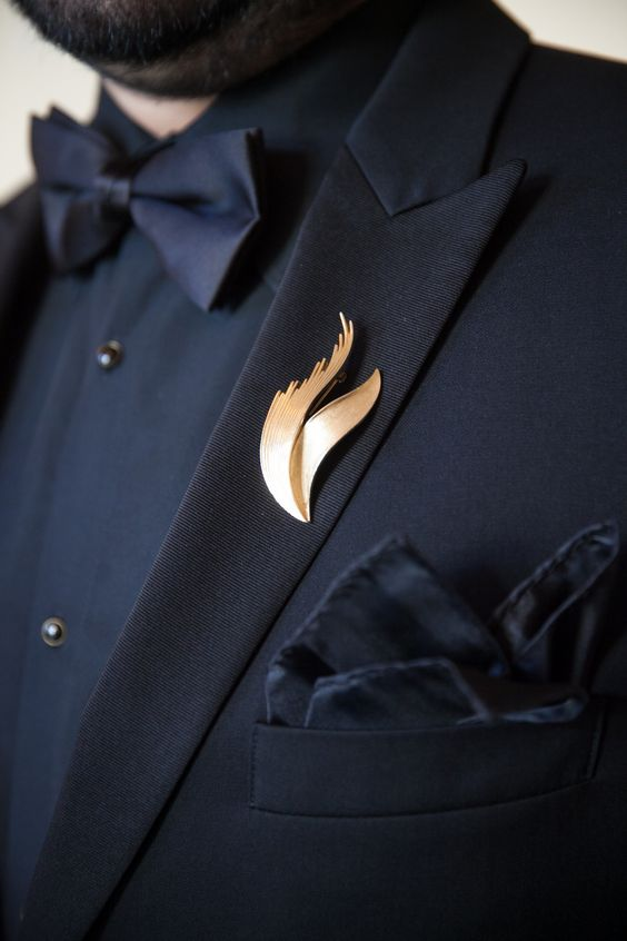 a refined gold wedding boutonniere of curves is a bold way to accent a total black look
