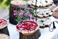 a relaxed and natural pie bar with tree stumps as pie stands, a stand with mini cakes and bright blooms in vases is great for summer