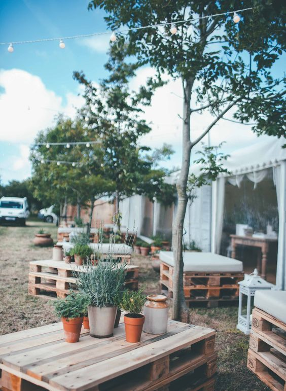 a relaxed rustic wedding lounge made of pallets, with lanterns and potted greenery is a very budget-friendly idea