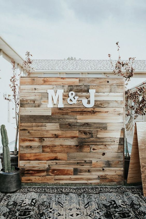 a rustic boho wedding backdrop made of stained pallet wood and monograms plus cacti around is a trendy idea