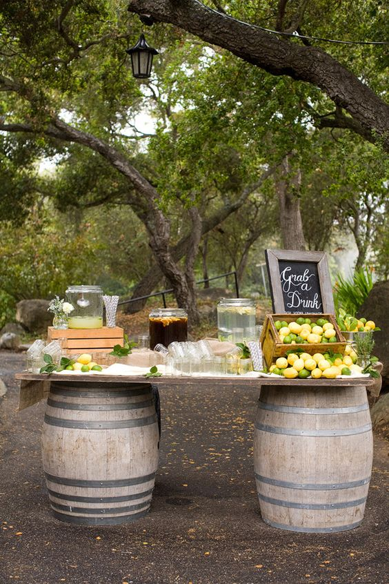 a rustic wedding lemonade bar of a couple of barrels, a tabletop with fruits and fresh drinks is perfect
