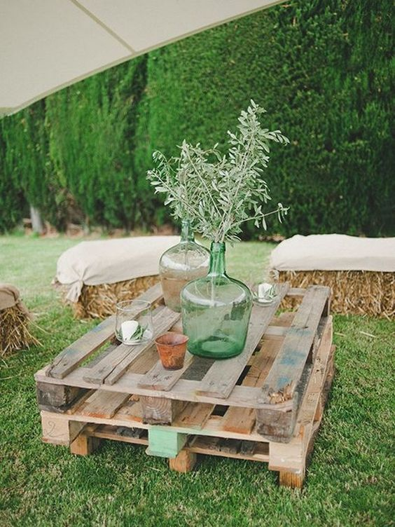 a rustic wedding lounge with hay covered with fabric and a low picnic table made of pallets
