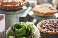 a simple and a bit rustic pie bar with wooden boxes with white blooms and succulents, metal stands with pies and plates is a cool idea