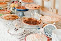 a simple and cute pie bar with a doily tablecloth, letters, paper fans and lots of pies and cookies with tags
