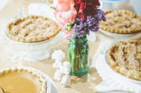 a simple and relaxed pie bar with doilies, bright blooms in a jar and white stands with pies is a very cool idea