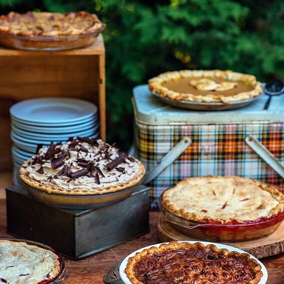 a simple and rustic pie bar with crates, boxes and plaid lunch boxes is ideal for a camp wedding or a woodland one