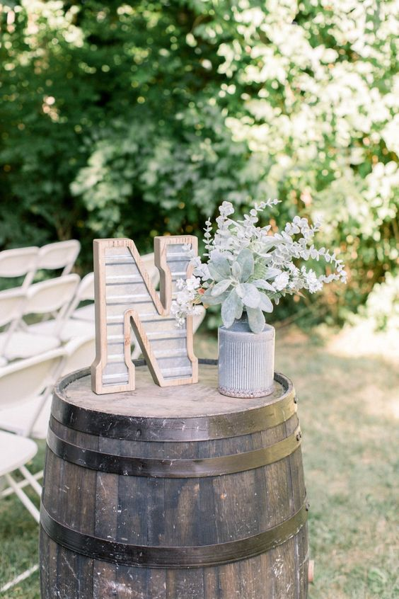 a simple rustic wedding decoration of a barrel, a metal monogram and pale greenery in a vase is lovely