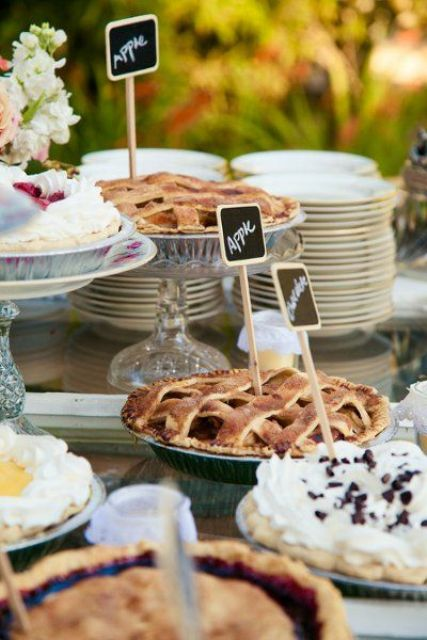 a simple summer wedding pie bar with plates, chic glass stands and chalkboard topper and some blooms