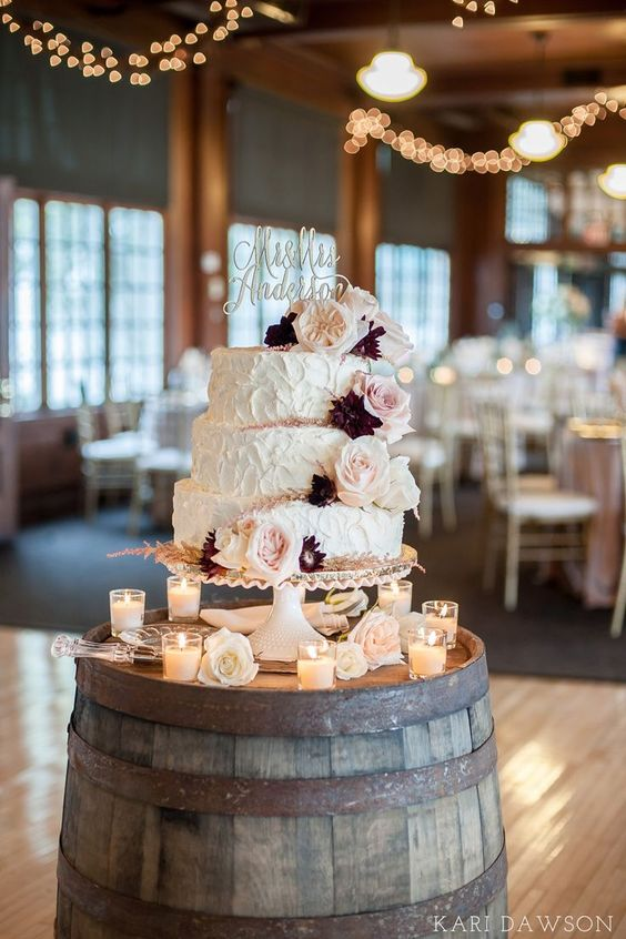 a simple vintage wedding cake stand - a barrel with blooms and candles and a gorgeous wedding cake with a calligraphy topper