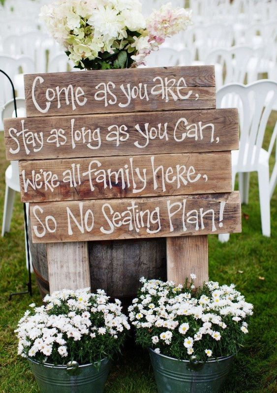 a simple wedding ceremony space sign made of pallet wood and with potted blooms in buckets around
