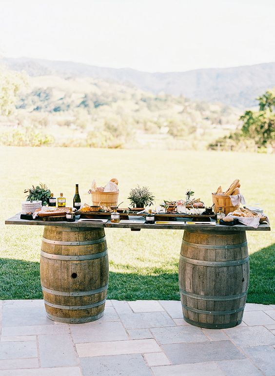 a simple wedding cocktail bar with wine barrels and a tabletop, baskets with bread, wine, appetizers and other stuff