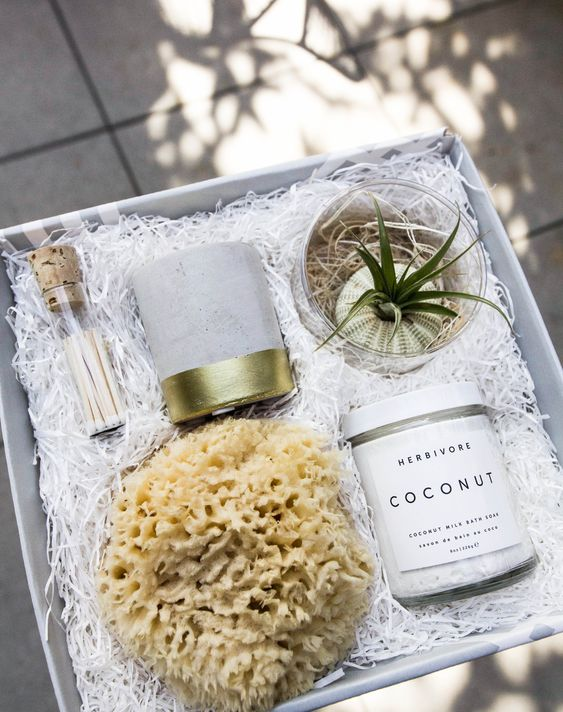 a spa box favor with an air plant, a foam, a candle in a concrete candleholder and some luxurious bath salts