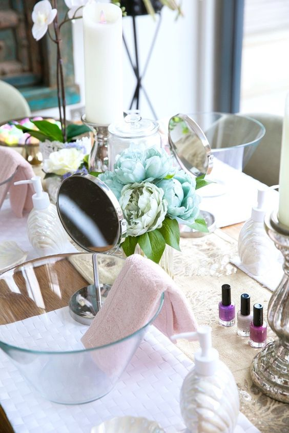 a spa bridal shower setting with pastel blooms, glass bowls, mirrors, nail polishes and potted orchids and candles
