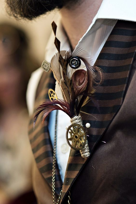 a steampunk wedding boutonniere of feathers, gears and buttons plus an additional gear for an accent