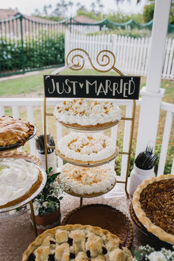 a summer rustic pie bar with elegant metal stands and white blooms in tin jars, cutlery in jars and some greenery is cool