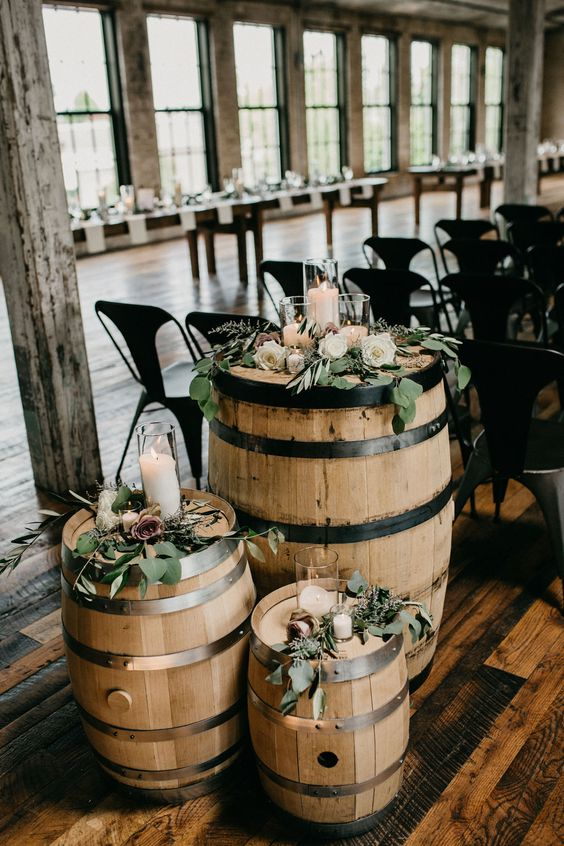 a trio of barrels with greenery, pastel and white blooms and candles is a lovely decoration for an indoor or outdoor wedding