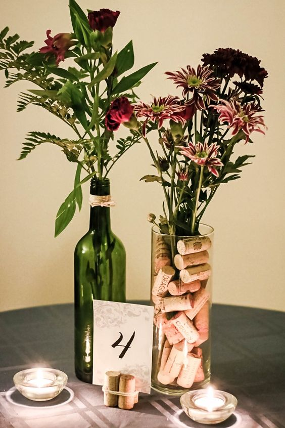 a vineyard wedding centerpiece of wine corks with a table number, bright blooms and greenery in a bottle and vase with corks