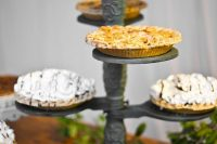 a vintage wedding pie bar with a metal stand and lots of pies, some neutral blooms and greenery is very elegant