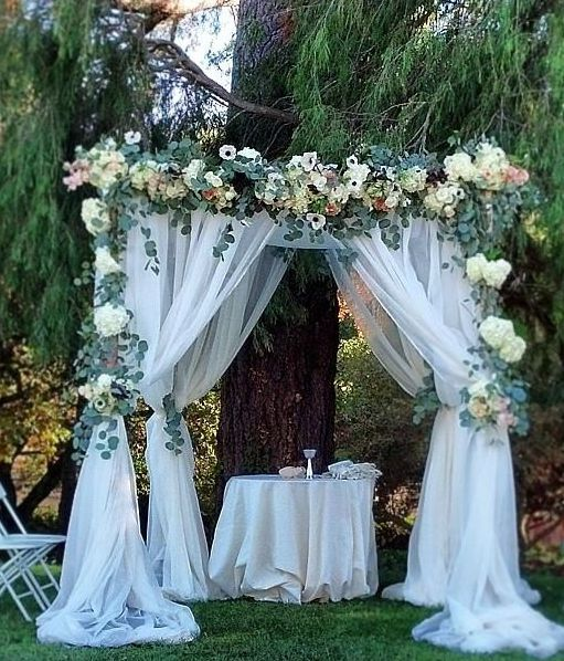a wedding arch with white tulle curtains, lush greenery and neutral blooms is ideal for a rustic wedding