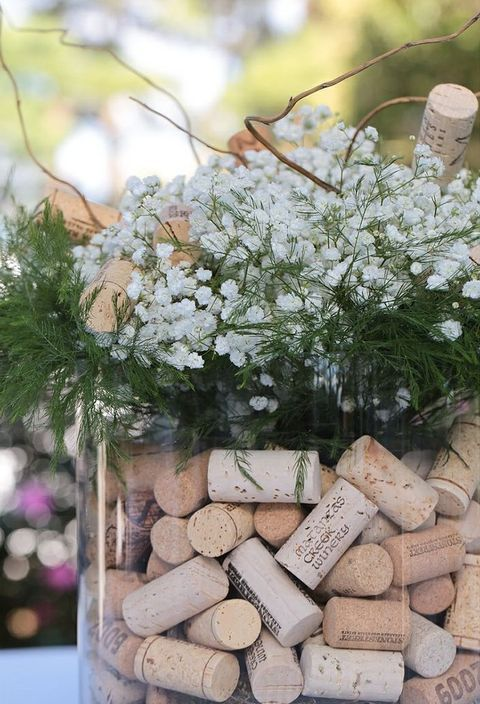 a wedding centerpiece of a large jar with wine corks, baby's breath, greenery and twigs for a vineyard wedding