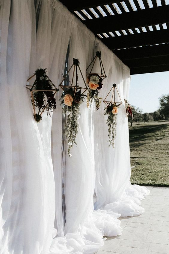 a wedding ceremony backdrop of tulle curtains, geometric floral hangings and lush blooms and greenery