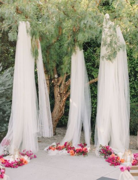 a wedding ceremony space done with tulle curtains and bold lush blooms plus some candle holders