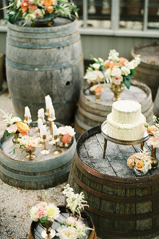 a wedding dessert table styled in a creative way, with barrels, neutral and pastel blooms, candles and a wedding cake on a stand