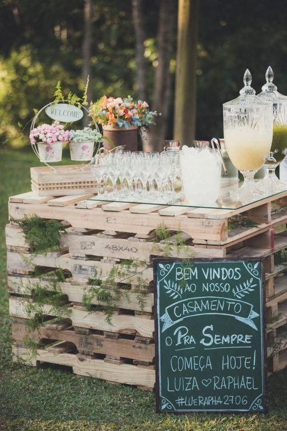 a wedding drink bar of pallets and ferns in between, with a chalkboard sign and floral arrangements on top