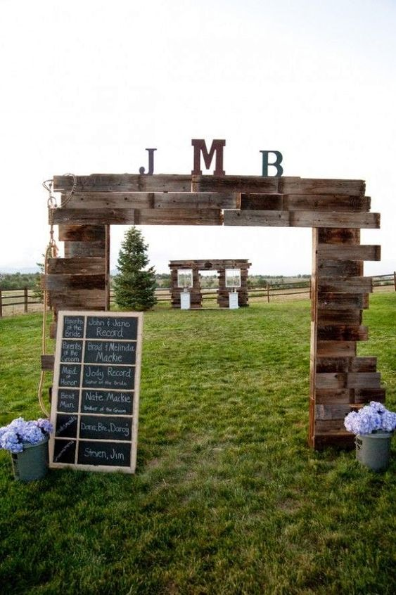 a wedding gate built of stained pallets with monograms and a chalkboard sign plus blooms in buckets