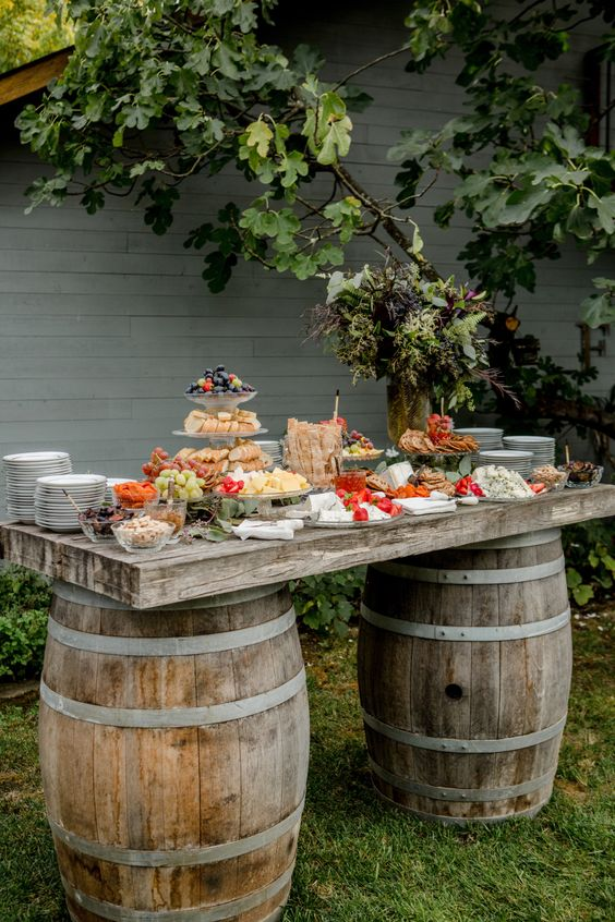 a wedding grazing table of two barrels and a rustic tabletop with delicious food, plates and tiered stands is a lovely idea