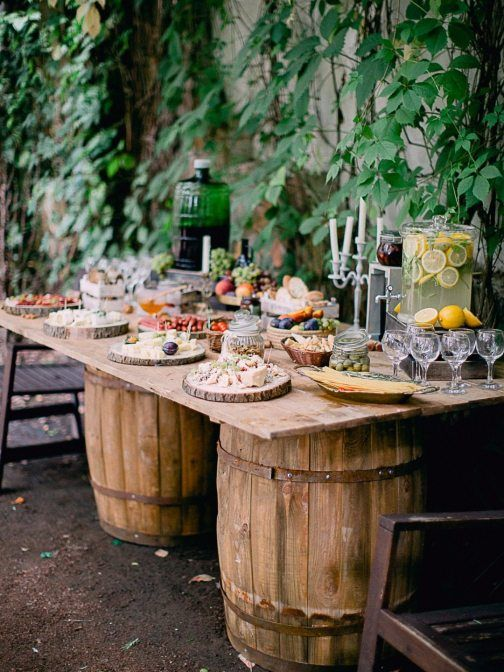 a wedding grazing table of wine barrels and a tabletop, with candles, tasty food and appetizers is a pretty idea for a rustic wedding