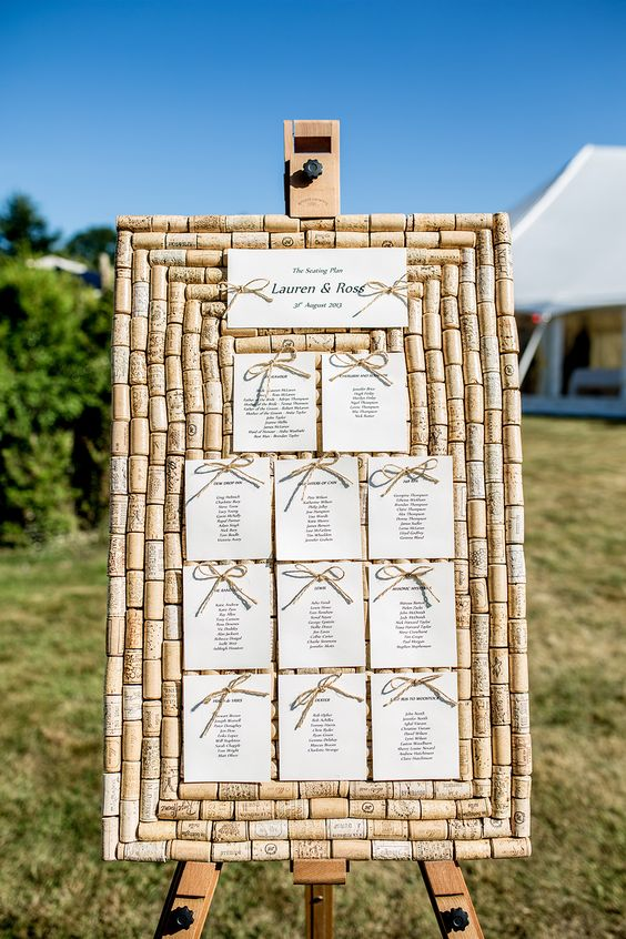 a wedding seating chart fully made of wine corks and with paper and bows is a cool and bold idea