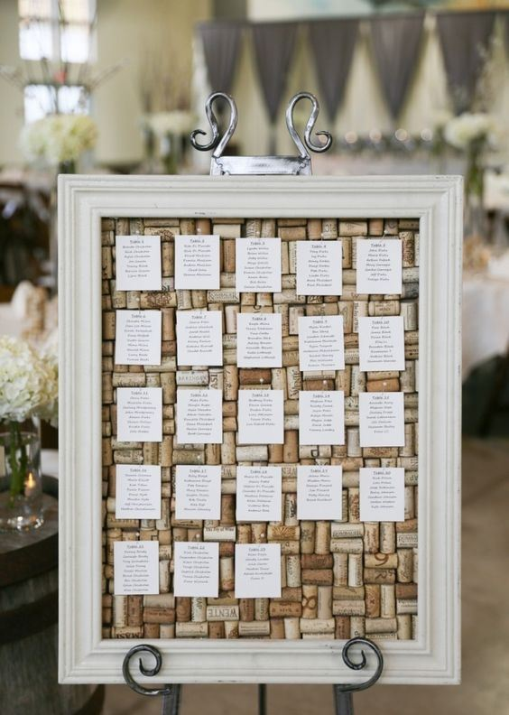 a wedding seating chart with wine corks and paper in a large frame is a stylish and chic idea