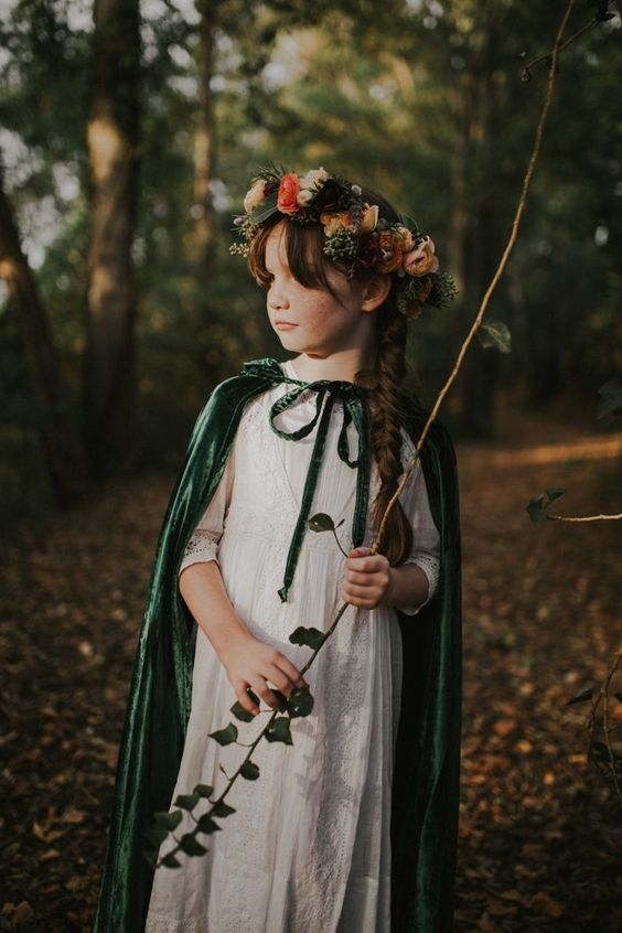 a white boho lace A-line maxi dress, a green velvet cloak and a floral crown for a winter fairy tale wedding