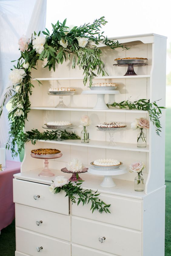 a white buffet with greenery and white blooms, blush blooms in jars and various stands with pies is amazing for a wedding
