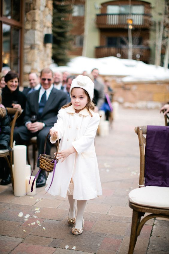 a white coat, a white beanie, shiny flats and a neutral dress for a comfortable winter flower girl look