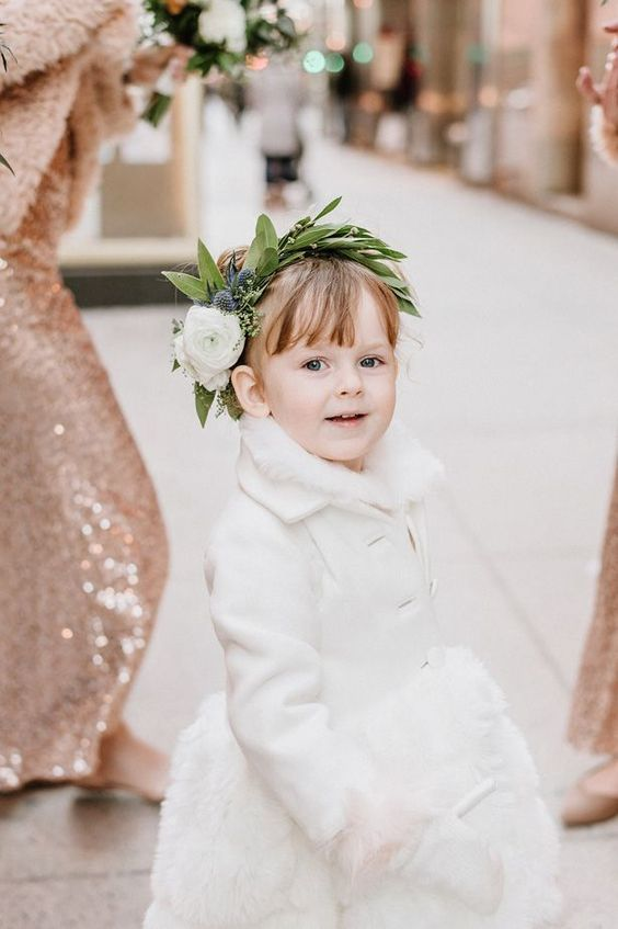 a white coat, a white faux fur skirt, white mittens and a greenery and flower crown for a refined look